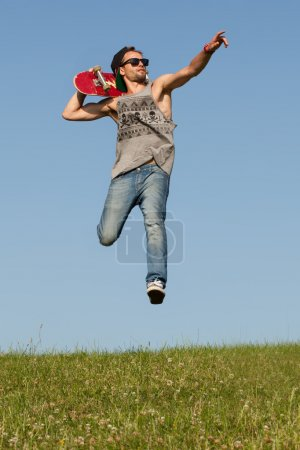 Man with a skateboard pointing and leaping