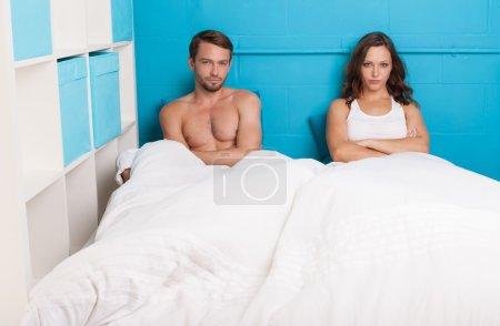 Pessimistic couple having an argument sitting on bed