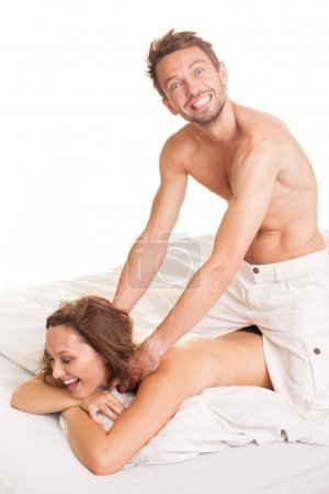 Photo for Playful man giving his wife a massage kneeling over her in bed manipulating her shoulder muscles as she lies laughing on the bed - Royalty Free Image