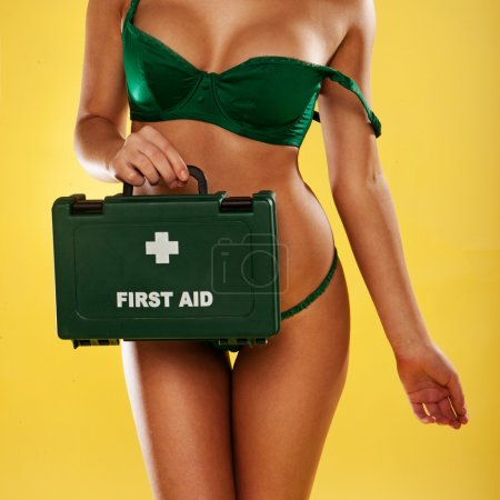 Sexy busty woman with a first aid kit