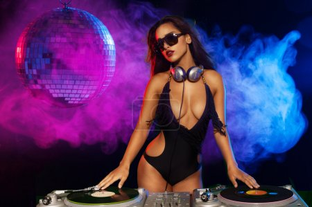 Photo for Glamorous sexy busty DJ at work mixing sound on her decks at a party or night club with colourful smoke light background - Royalty Free Image