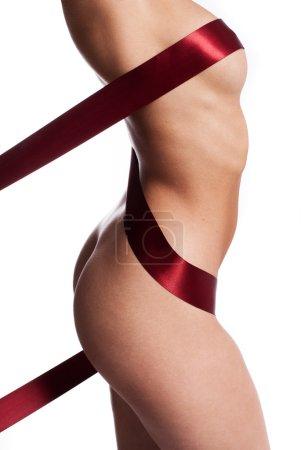 Photo pour Ruban rouge artistiquement enroulé autour d'un corps de femme nue dissimuler le mamelon et accentuer les courbes de womans et les fesses sexy, vue de côté du torse isolé sur blanc - image libre de droit