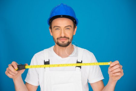 Smiling workman holding a tape measure