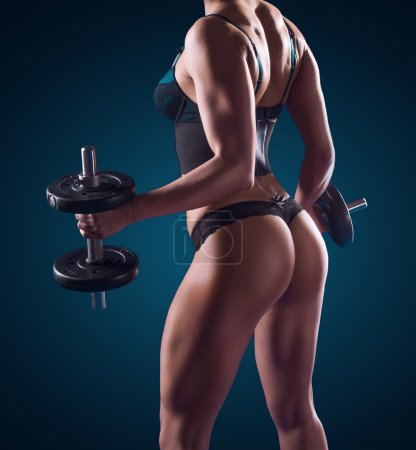 Muscular athletic woman working out with weights