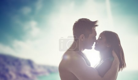 Photo for Silhouettes of the head and shoulders of a romantic young couple kissing backlit by the sun with a coastal backdrop - Royalty Free Image