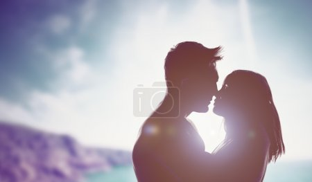 Loving couple backlit by a bright sun
