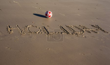 The word holiday written on the sand of a beach