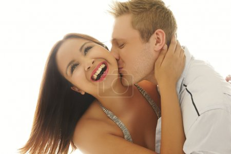 Laughing woman being kissed by her lover