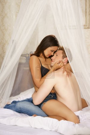 Loving couple sitting on the bed embracing under a...