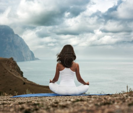 Photo for Young Woman in Lotus Position near the Ocean. Rear View - Royalty Free Image
