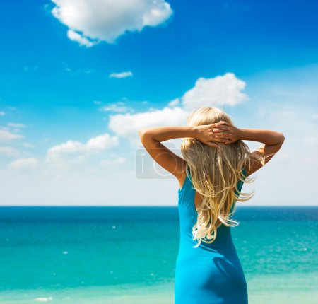 Woman in Turquoise Dress at the Sea. Rear View.