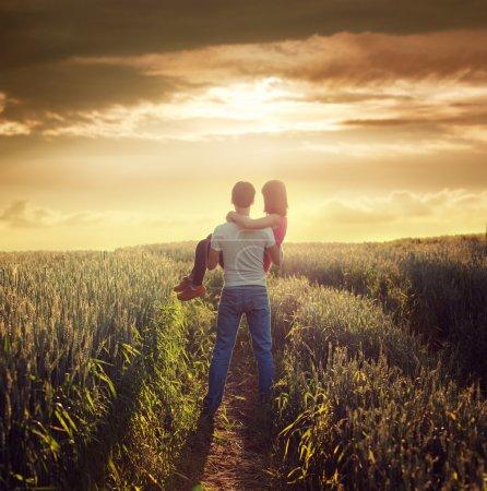 Photo pour Homme porte femme au champ de l'été au coucher du soleil. l'amour romantique et le concept de soins. espace de la copie. photo tonique. - image libre de droit