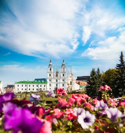 Photo pour Cathédrale Saint-Esprit à Minsk, Biélorussie. Vue de l'église orthodoxe et du centre historique (Nemiga). Fleurs déconcentrées au premier plan . - image libre de droit