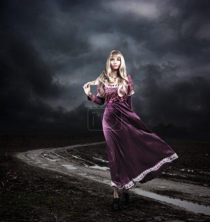 Woman in Purple Dress Walking on Dirty Road