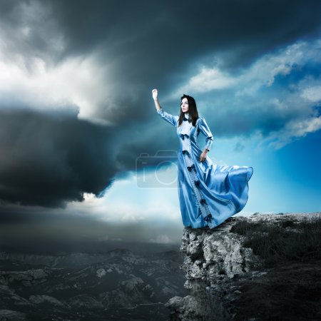 Photo for Full Length Photo of Fantasy Woman in Waving Blue Dress Reaching for the Light. Dramatic Moody Sky. HDR Cloudscape. - Royalty Free Image