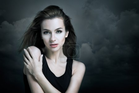 Lonely Woman on the Background of Dark Clouds