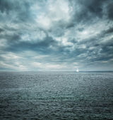 Sailing Boat at Stormy Sea. Dark Background.