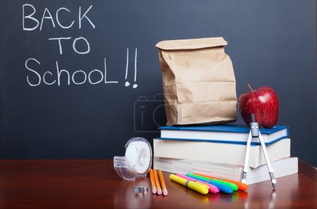 Photo for Back to school, school books with apple and paper bag lunch on des - Royalty Free Image