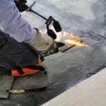 Man applying waterproof coating in a building site...