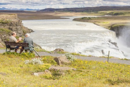 Gullfoss waterfall and two man on the wooden bench - Iceland.