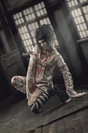 Photo for Insane girl in bloody straitjacket - Royalty Free Image