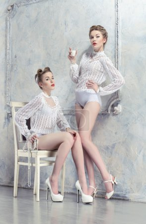 Photo for Two pretty women in white costumes posing in white room - Royalty Free Image