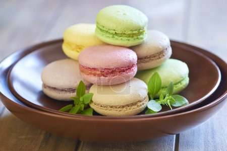 Photo for Tasty colorful French macaroons on brown plate - Royalty Free Image