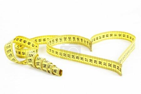 Photo pour Un ruban à mesurer formant un cœur isolé sur fond blanc - image libre de droit