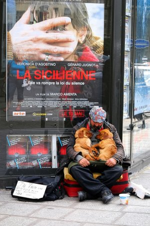 PARIS - May 7: A homeless man sitting on the street with a dog a