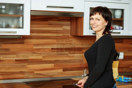 Foto de Feliz sonriente mujer de mediana edad limpia los platos en la cocina - Imagen libre de derechos