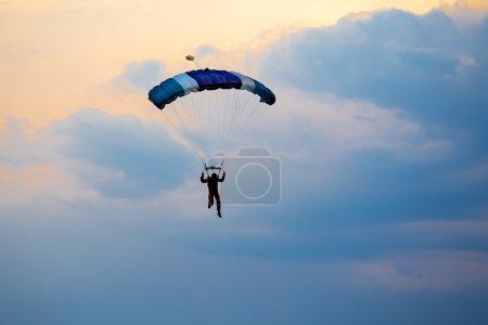 Photo pour Silhouette de parachutiste parachutiste non identifié sur ciel bleu au coucher du soleil - image libre de droit