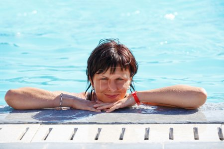 Smiling middle age woman relaxing in swimming pool