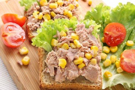 Sandwich with tuna and corn on wood background