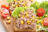 Sandwich mit Thunfisch und Mais auf Holz-Hintergrund