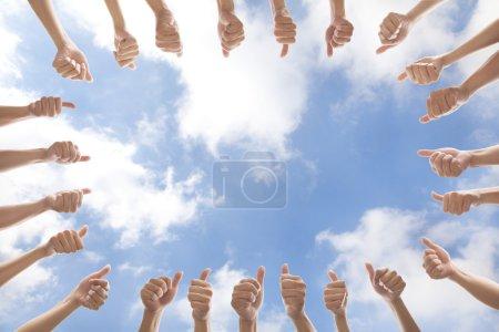 Foto de Grupo de con los pulgares para arriba en el fondo de la nube - Imagen libre de derechos