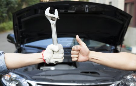 Hand of mechanic with thumbs up and tool