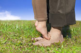 Family feet on the grass with cloud background