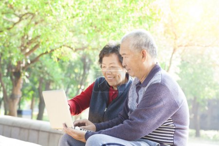 Happy Senior couple surfing on internet with laptop