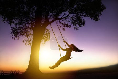 Photo for Silhouette of happy young woman on a swing with sunset background - Royalty Free Image