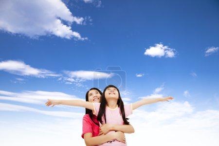 Photo pour Heureuse petite fille et mère regarder le ciel - image libre de droit