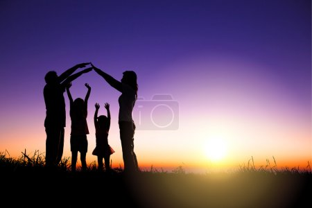 Happy family making home sign on the hill with sunrise backgroun