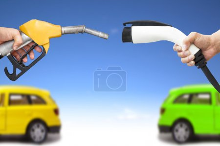 electric car and gasoline car concept. hand holding gas pump and