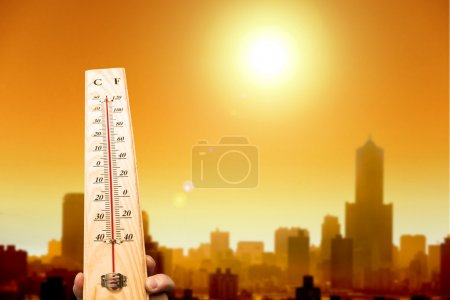 Heat wave in the city and hand showing thermometer...