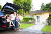 Az autó és a ház mögött ül boldog család