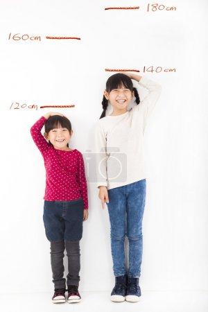 Foto de Niñas felices creciendo y contra la pared - Imagen libre de derechos