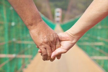 Photo for Senior man with woman couple holding hands walking on the bridge - Royalty Free Image