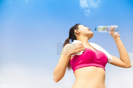 Sporty woman drinking water bottle after jogging or running
