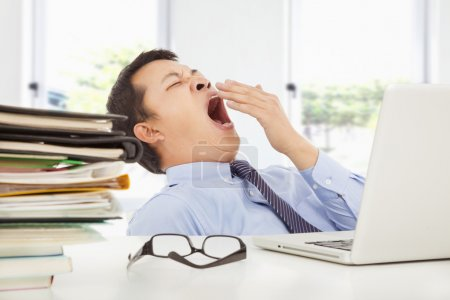 Exhausted young businessman yawning at work in office
