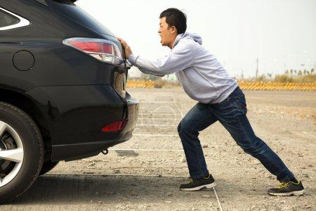 Man pushing a broken car down the rock road