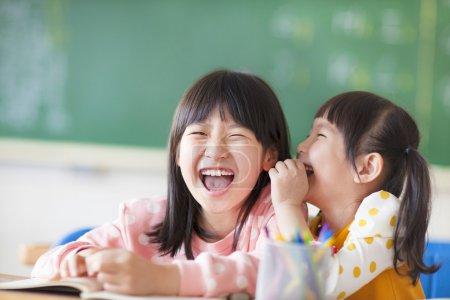 Photo pour Rire de petites filles partageant des secrets en classe - image libre de droit